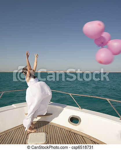 Bride releasing balloons from a boat - csp6518731