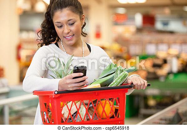frau- einkaufen, handy, gebrauchend, lächeln, kaufmannsladen - csp6545918