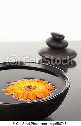 Orange gerbera floating on a black bowl and a stack of black pebbles - csp6567454