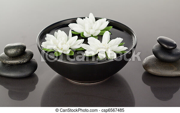 Close up of flowers floating surrounded by stacks of black pebbles - csp6567485