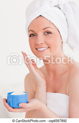 Charming young woman wrapped in a towel using skin cream - csp6567892
