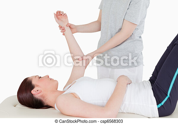 Sportswoman having her arm stretched by a masseuse - csp6568303