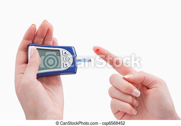 Close up of a blood glucose meter utilization - csp6568452