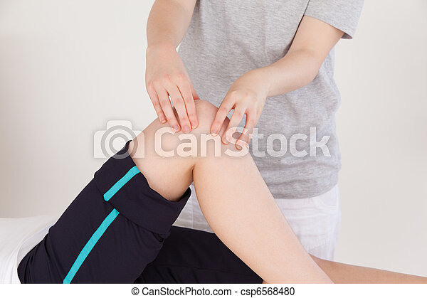 Close up of a masseuse massing the knee of an athletic woman - csp6568480