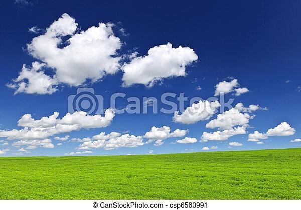 Green rolling hills under blue sky - csp6580991