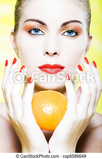 Woman portrait holding a orange tangerine citrus fruit - csp6586649