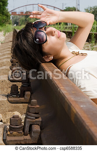 Girl in sunglasses laying carelessly on the railroad - csp6588335