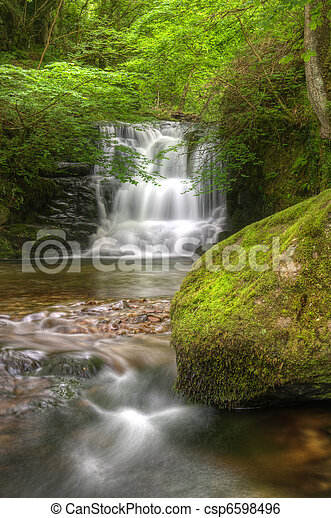 Lush green forest scene with long exposure blurred waterfall flowing through and over rocks covered in lichen and moss - csp6598496