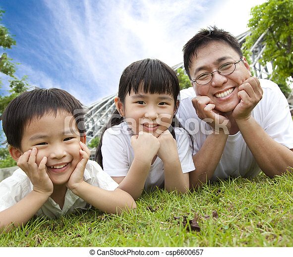 happy family lying on the grass.father with son and daughter - csp6600657