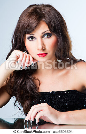 Portrait of attractive young brunette woman with long hair and beautiful nails art wearing black sitting on a blue background - csp6605894