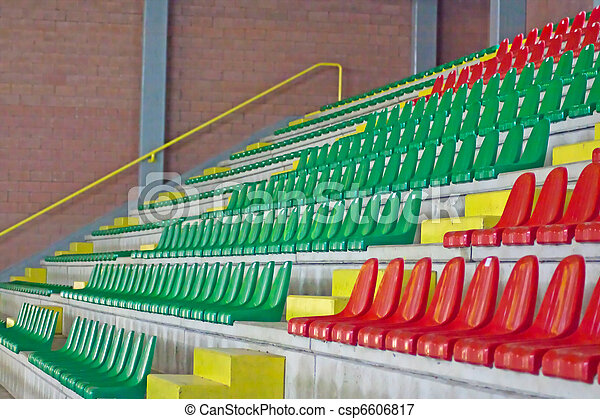 Green and red empty seats of an arena