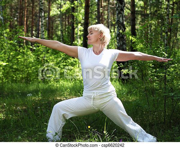 An elderly woman practices yoga - csp6620242