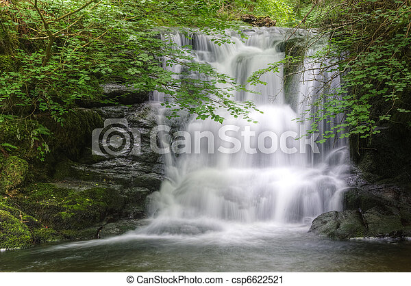 Lush green forest scene with long exposure blurred waterfall flowing through and over rocks covered in lichen and moss - csp6622521