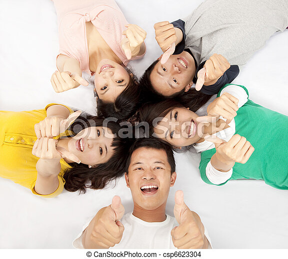 group of asian young people lying together with thumb up - csp6623304