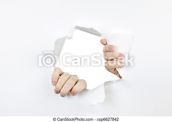 Hands ripping through hole in paper - csp6627842