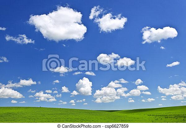 Green rolling hills under blue sky - csp6627859