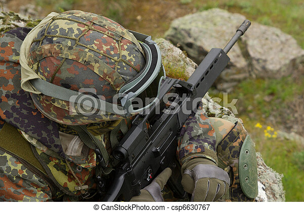 Soldier with a rifle sitting - csp6630767