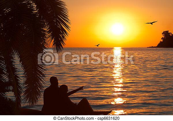 Loving couple watching beautiful sunset on seashore - csp6631620