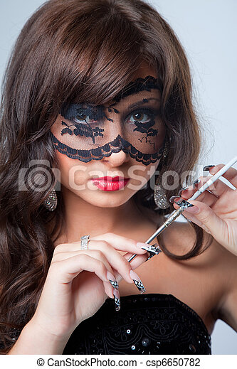 Closeup portrait of attractive young brunette girl with long dark ringlets and fine art manicure wearing lacy mask on her eyes holding graceful silver mouthpiece with thin ladies' cigaret on blue bac - csp6650782