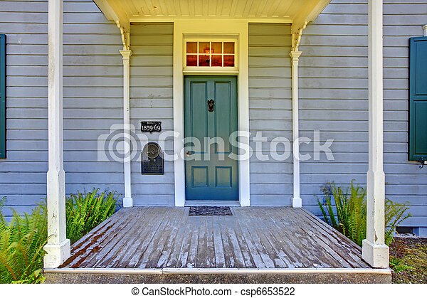 Grey historical house front entrance with green door. - csp6653522