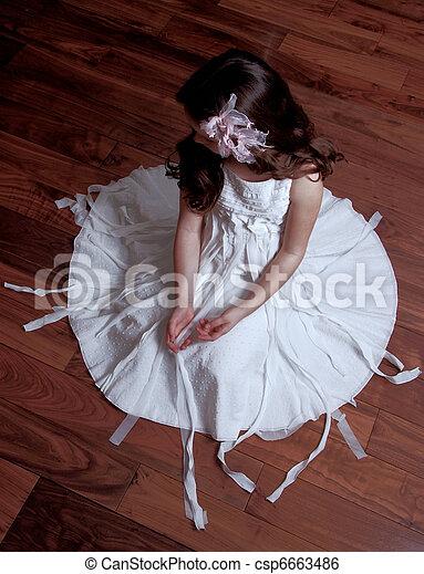 Girl wearing neat dress sitting on wooden floor - csp6663486
