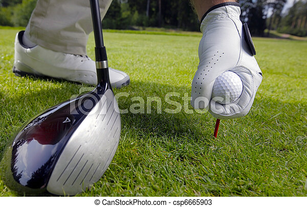 hand placing a tee with golf ball  - csp6665903