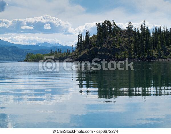 Yukon wilderness reflected on calm lake - csp6672274