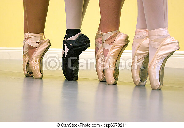 Four ballerinas are standing on their toes on pointe wearing ballet