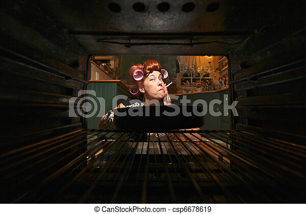 Funny Housewife Smoking and Cooking Dinner in a Vintage Oven - csp6678619