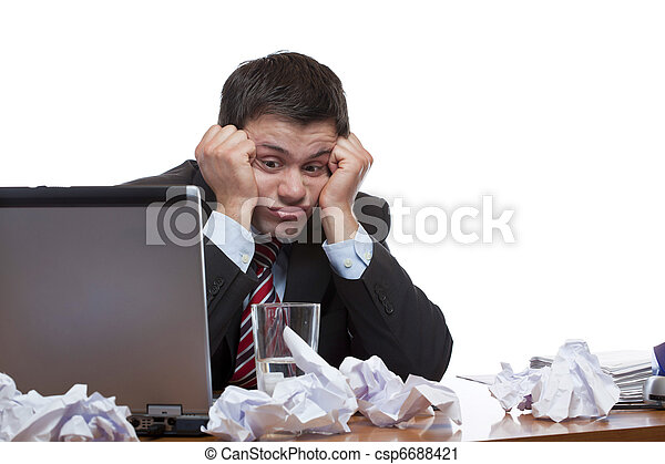Desperate, frustrated man sitting with paperwork at desk in office. Isolated on white background. - csp6688421