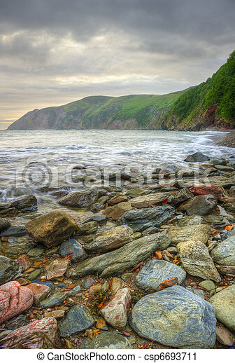 Beautiful warm vibrant sunrise over ocean with cliffs and rocks - csp6693711