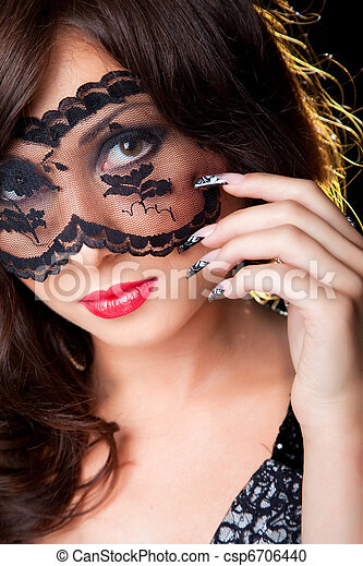 Closeup portrait of attractive young brunette girl with long dark ringlets fine art manicure wearing lacy mask on her eyes - csp6706440