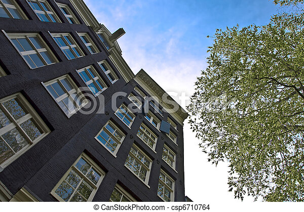 Old residential house in Amsterdam. Perspective shot of a tree against the blue sky. Fragment - csp6710764