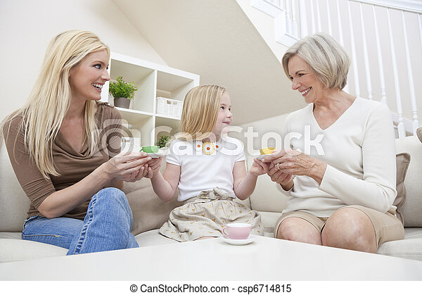 Three female generations of one family at home. Mother, grandmother and daughter who is playing at serving tea in a china tea set. - csp6714815