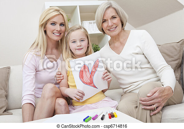 Three female generations of one family at home. Mother, grandmother and daughter who is holding a hand drawn picture of a red heart. Love or healthy living concept. - csp6714816