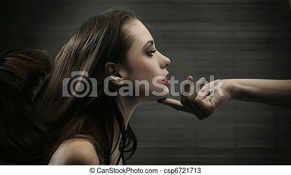 Conceptual image of a hand holding a woman's head - csp6721713
