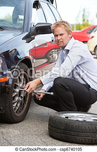 Business Man Replacing Tire - csp6740105