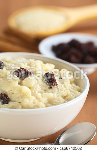 Delicious homemade rice pudding with raisins; with raisins, cinnamon sticks and raw rice on wooden spoon in the back (Selective Focus, Focus on the two raisins in the middle of the bowl) - csp6742562