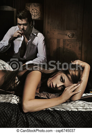 Sexy young woman laying on the bad and man drinking wine - csp6745037
