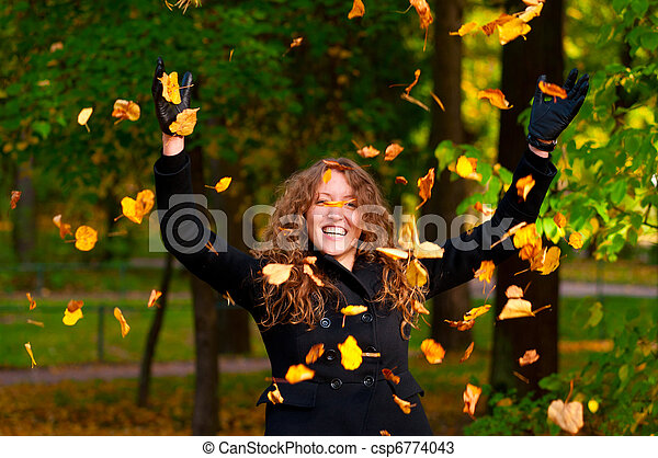 throwing dry autumn leaves in park - csp6774043