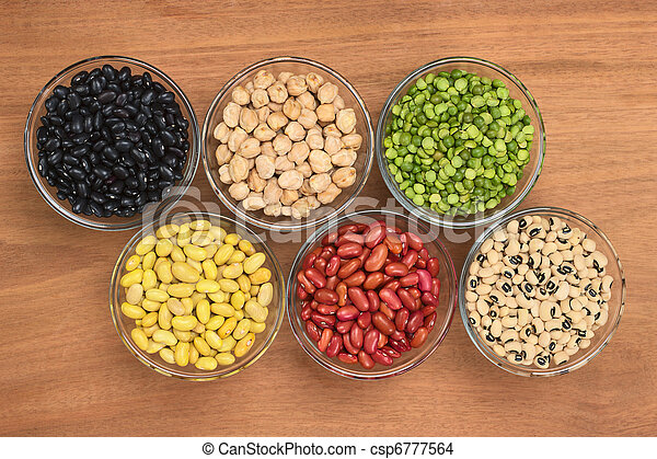A variety of legumes (black beans, chickpeas, slit peas, canary beans, kidney beans and black-eyed peas) in glass bowl photographed on wood from above  - csp6777564
