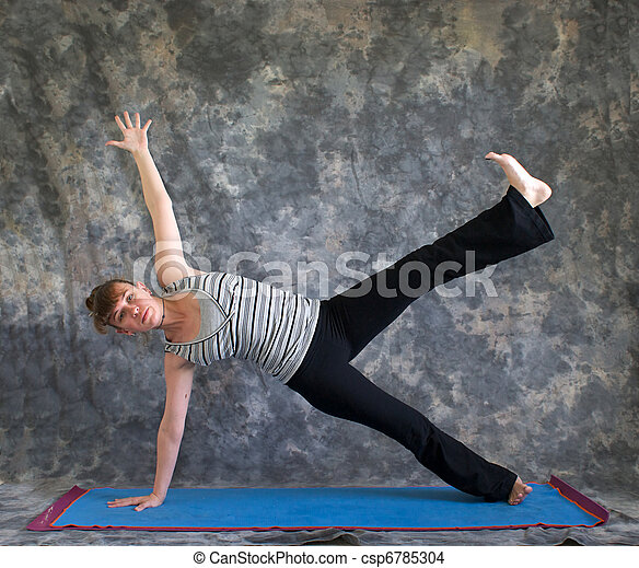 Young woman on yoga mat  doing Yoga posture Vasisthasana or side plank pose variation with arm and leg raised against a grey background front view, facing left lit by diffused sunlight. - csp6785304