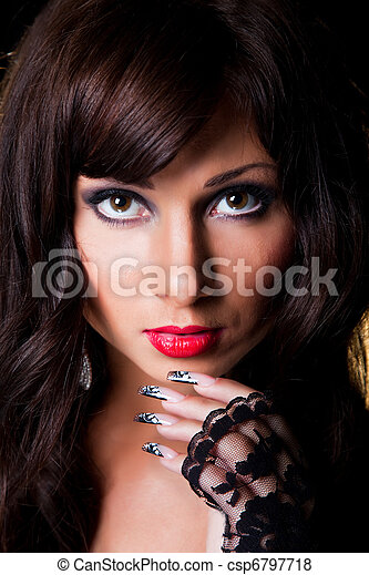 Closeup portrait of beautiful young brunette girl with long dark ringlets and fine art lacy manicure on black background - csp6797718
