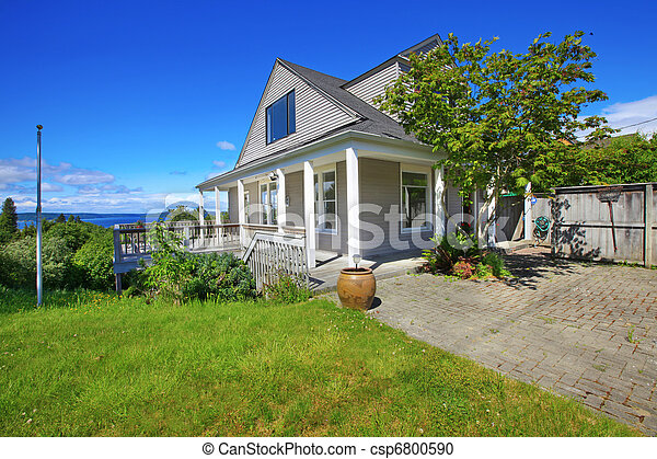 Grey house with white trim and water view. - csp6800590