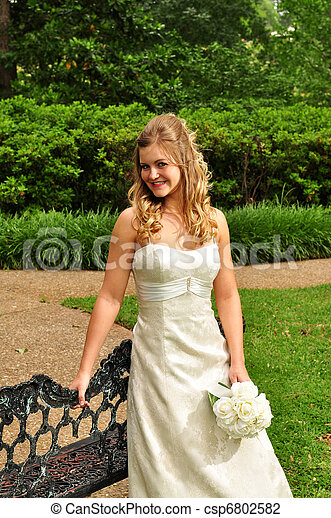 Caucasian bride 20s, standing outside by a bench - csp6802582