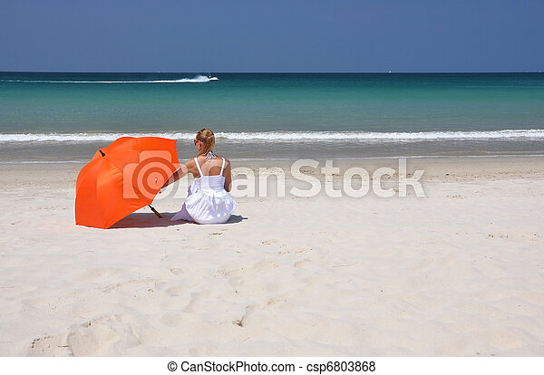 Girl with an orange umbrella on the sandy beach - csp6803868