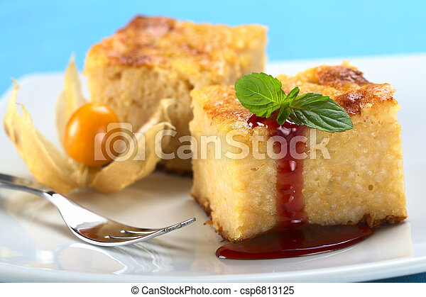 Baked rice pudding dessert with strawberry sauce and a mint leaf (Selective Focus, Focus on the front left edge of the cake, the strawberry sauce and the front of the mint) - csp6813125