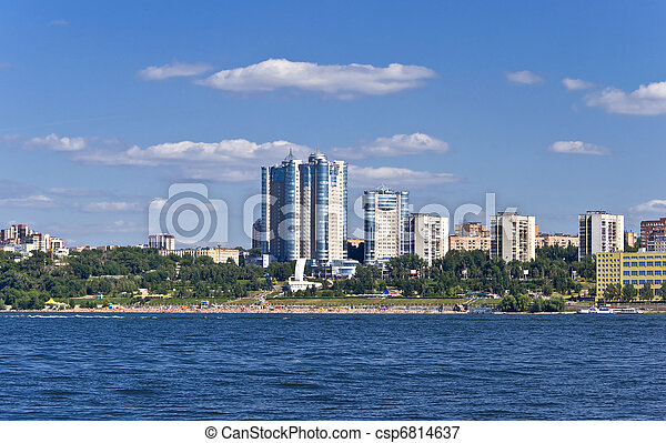 High apartment buildings on the quay. Beach filled with people. Summer urban landscape with a river. Samara. Russia. - csp6814637
