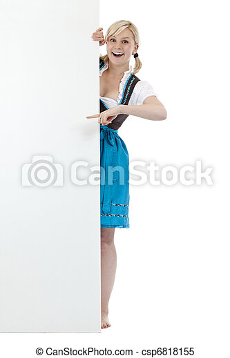 Young, blond woman in dirndl pointing surprised at billboard - csp6818155