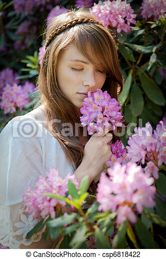 A young lady enjoys the smell of a rhododendron  blossom  - csp6818422